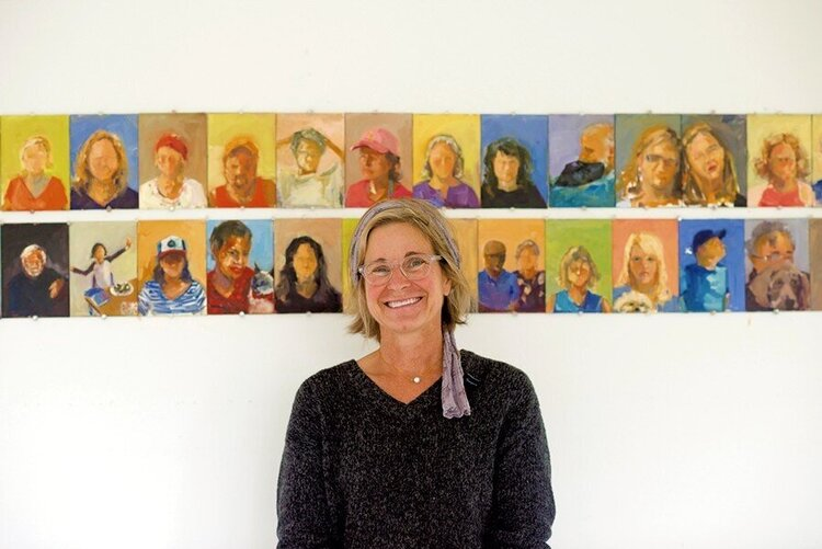 photo of Rebecca Kinkead standing in front of some of her Downtown Middlebury portraits